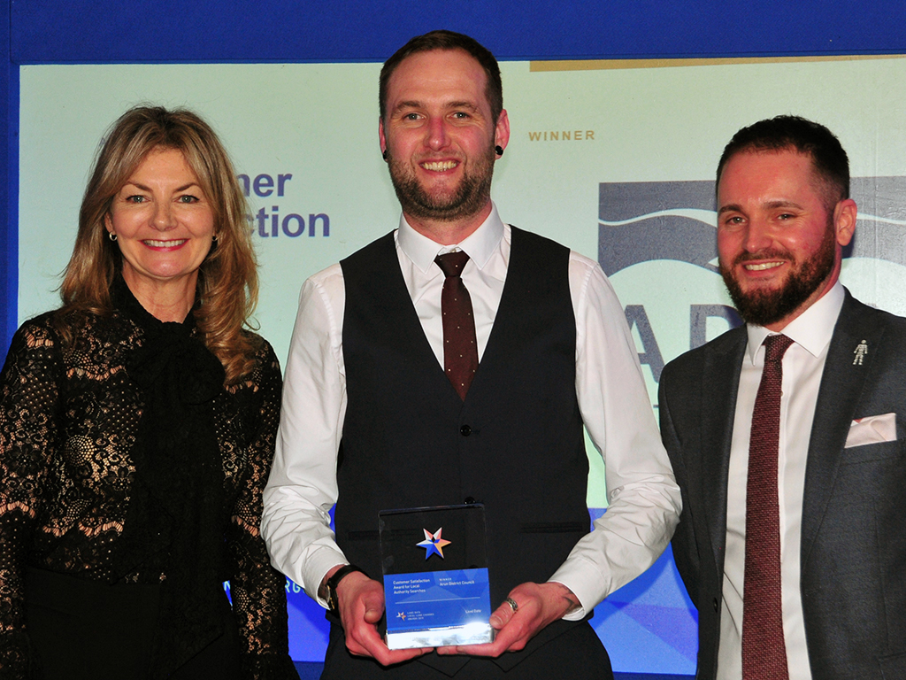 Andrew Simpson of the Coal Authority, right, with the awards host, comedian and writer Jo Caulfield, and Daniel Carmen from winners Arun District Council